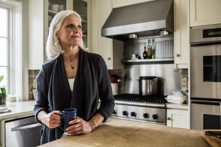 senior woman drinking coffee in kitchen