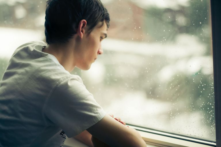 Young man gazes out window