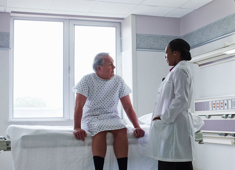 Black woman doctor talking to patient in hospital