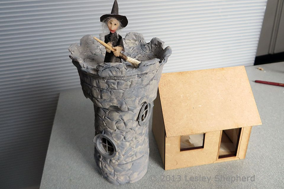 Model tower made from cardboard and air dry clay set beside a quarter scale Petite Properties Kit