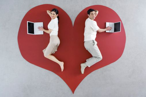 Pareja con portátil sobre un corazón gigante