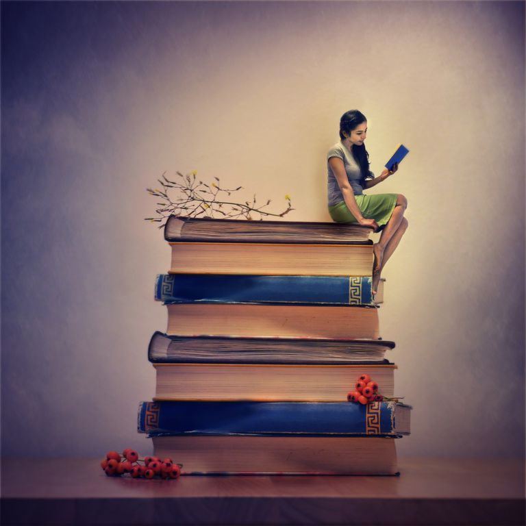 A woman sitting on a few giant books and reading