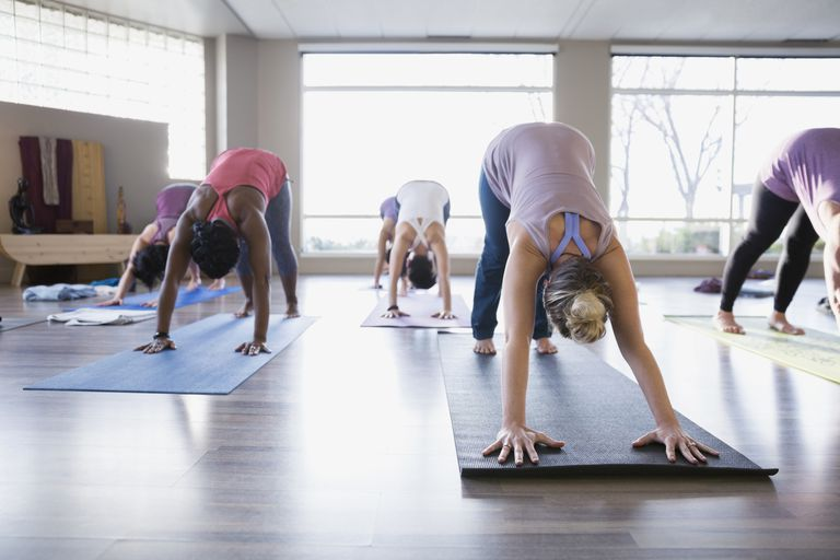 Women in a yoga class in downward facing dog position