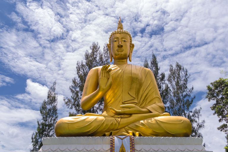 Low angle view of golden Buddha statue under cloudy sky