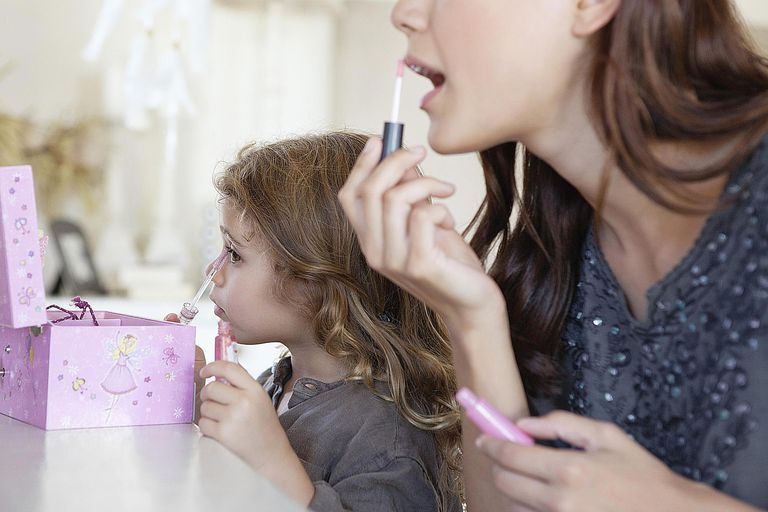 A young girl mimics her mother as they apply makeup. We learn from reference groups how what is normal and how to behave.