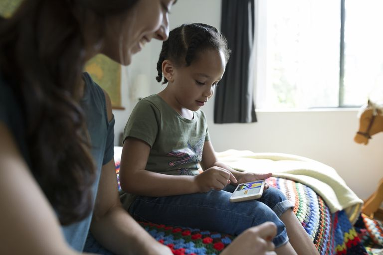 Mother and daughter playing video game on cell phone in bedroom