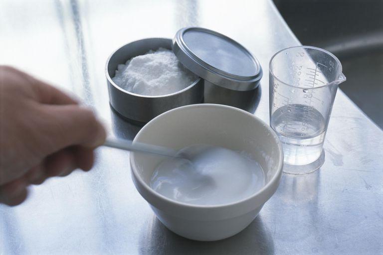 Making baking soda paste, mixing powder with water in bowl, close-up