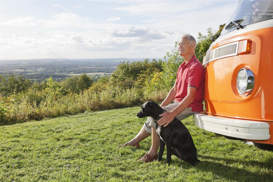 Senior man sitting by camper van with dog