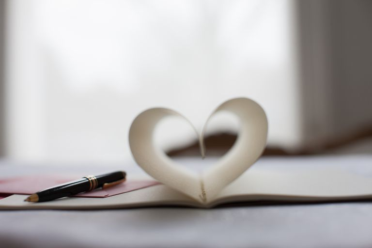 Pen and pages of notebook forming heart-shape Writing a romance novel? Romance is a billion dollar-a-year business.