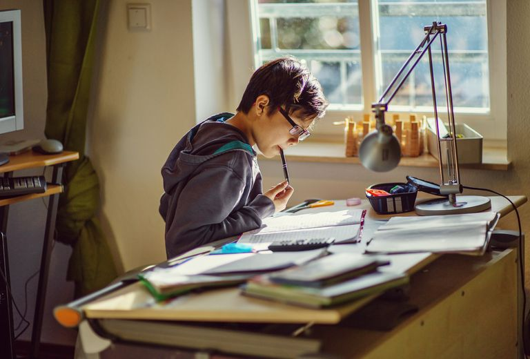 Boy doing his homework at desk in his room