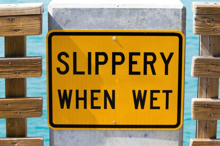 yellow sign reads Slippery When Wet