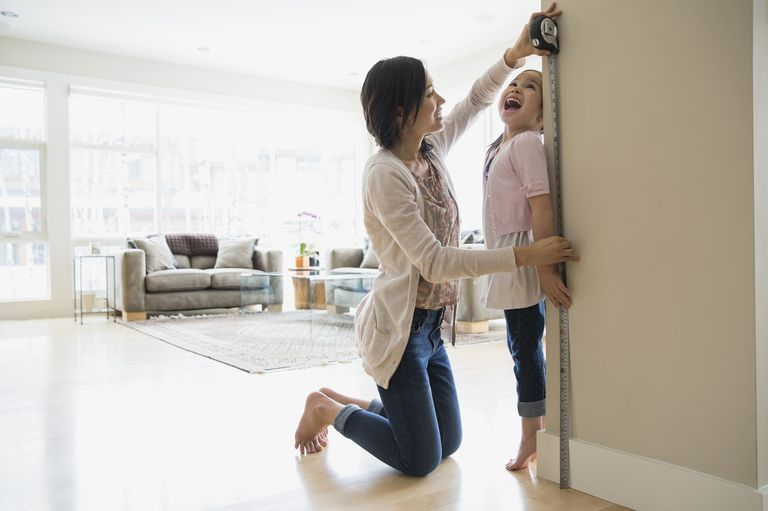 Mother measuring daughters height in living room
