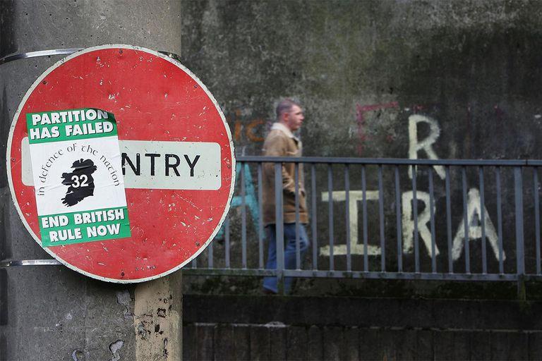 A sign with an IRA flyer adjacent IRA graffiti.