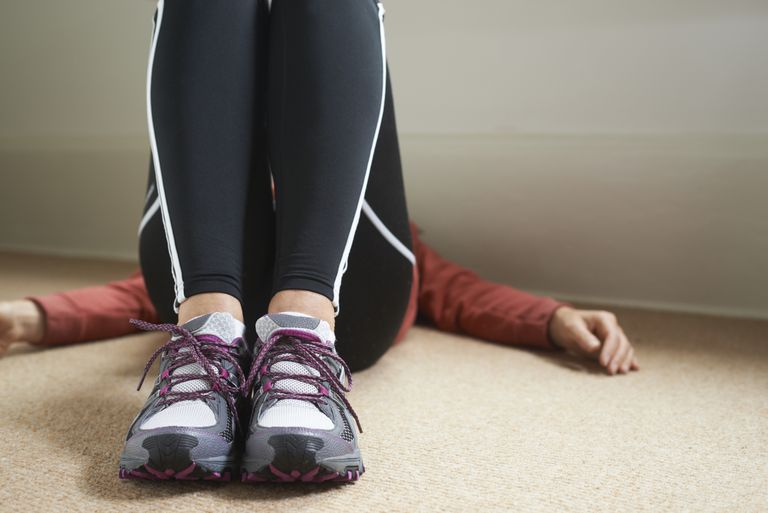 Woman in workout clothing lying on the ground
