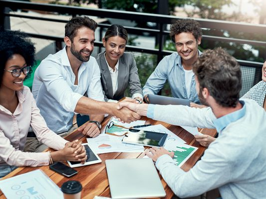Shot of businesspeople shaking hands during a meeting at a cafe