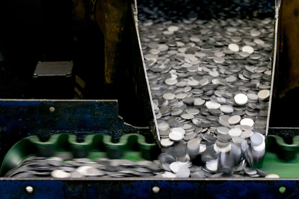 Blank coins that have been produced at the Royal Mint are sorted before being sent to be stamped in the coin press.
