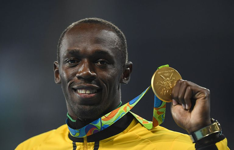 Usain Bolt holding up Gold Medal