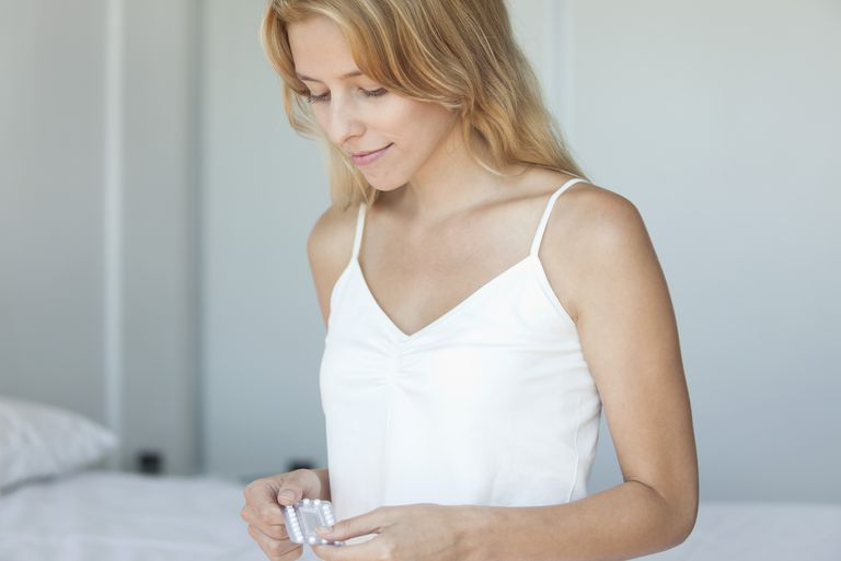 Young woman holding birth control pills