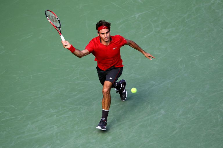 Roger Federer hits a forehand return against Novak Djokovic of Serbia during Day Thirteen of the 2011 US Open