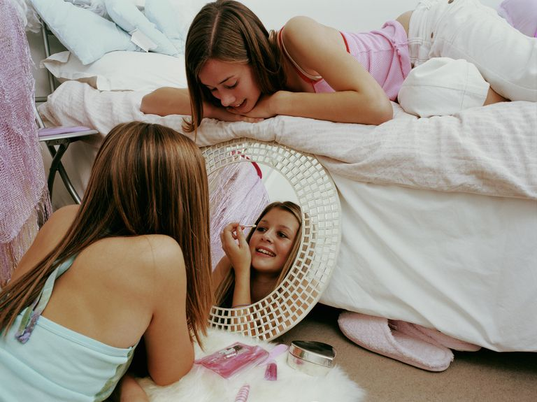 Two teenage girls using make-up in bedroom