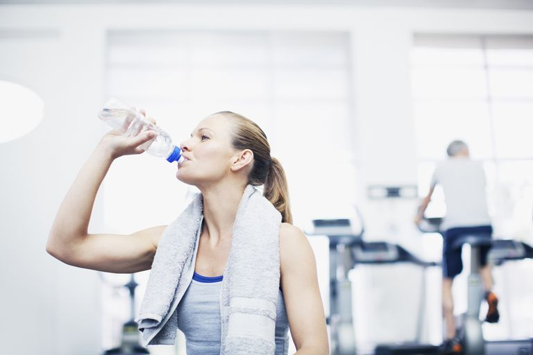 Woman drinking water after a workout at the gym