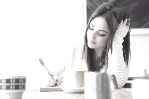 Young woman in cafe writing and drinking coffee