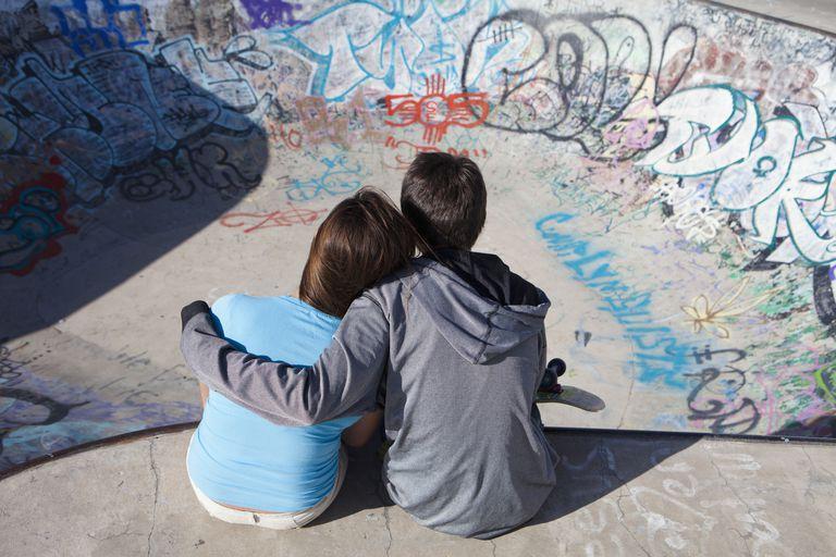 Boy and girl hugging in skateboard park