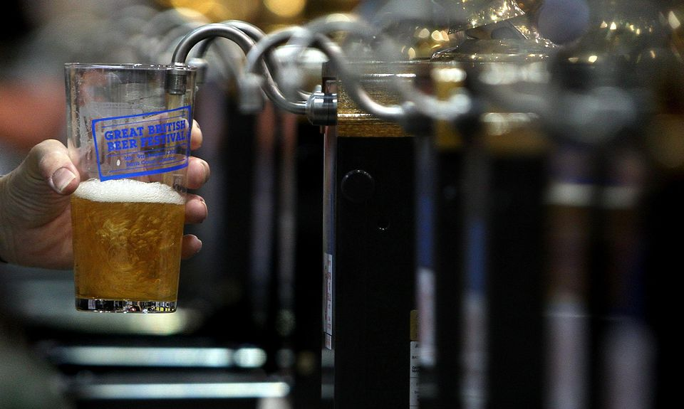 A barman pulls a pint of beer at the Great British Beer Festival