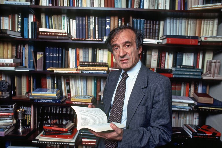 Elie Wiesel standing amongst bookshelves.