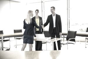 couple shaking hands with woman in office
