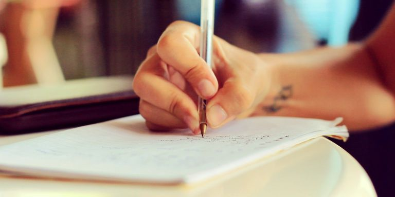 Close-up of hand writing in notebook