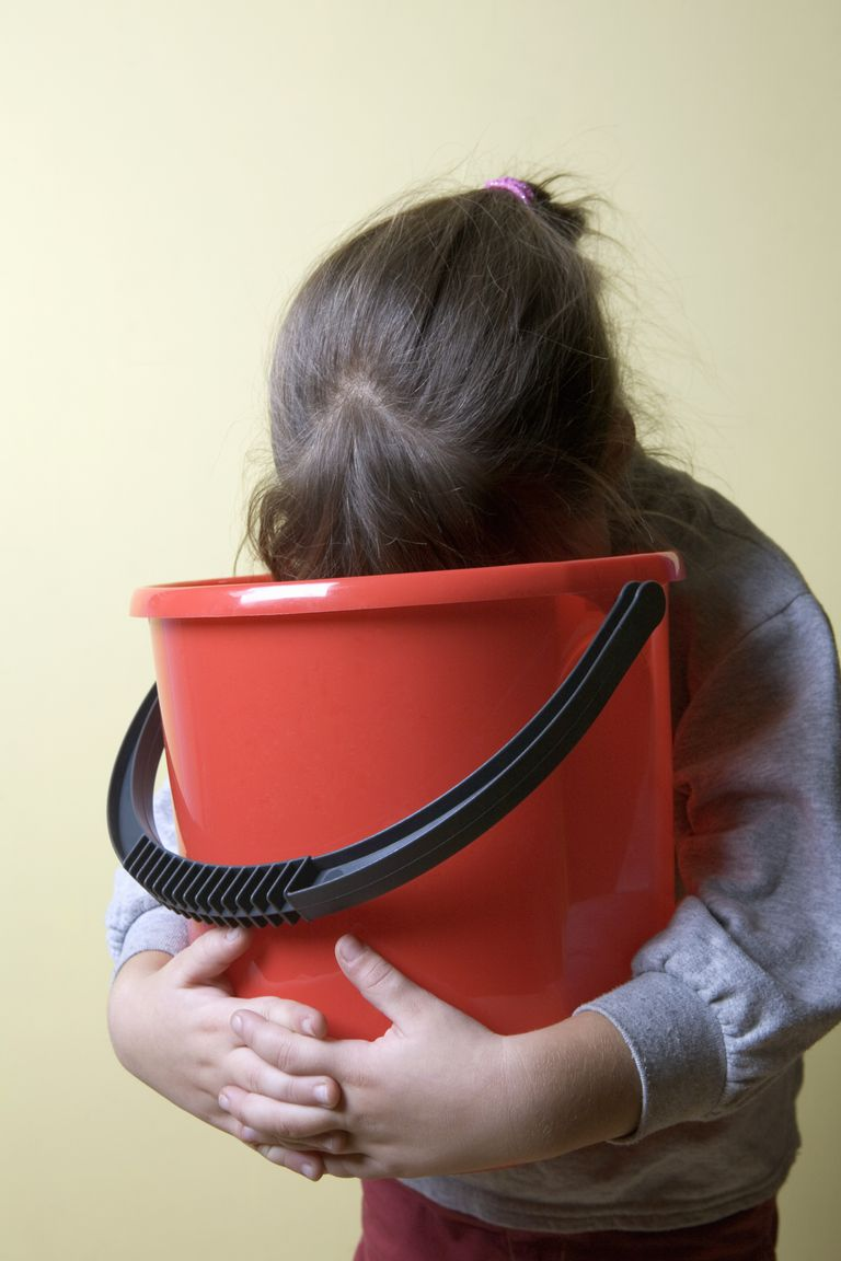 A young girl being sick in a bucket