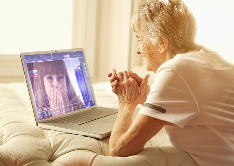 Older Caucasian woman video-chatting with granddaughter