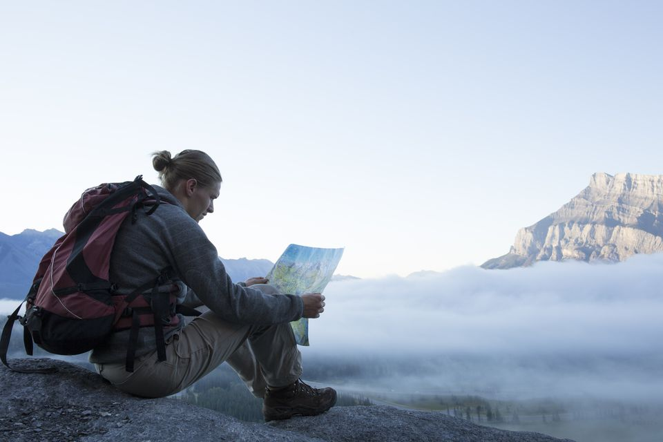 Hiker consults map on rock ledge, above mist
