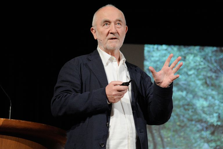 older white man with thin white beard speaking in front of an audience
