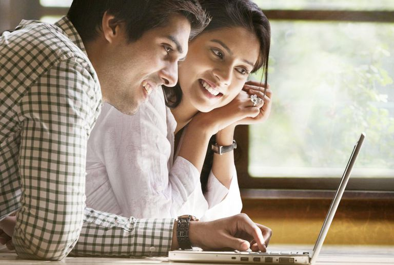 Happy young couple using laptop on floor at home
