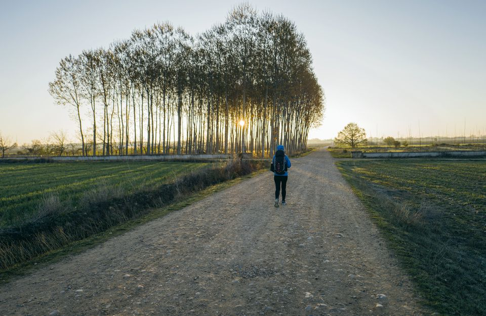 Woman walking along Camino de Santiago, Hospital de Orbigo, Leon, Spain