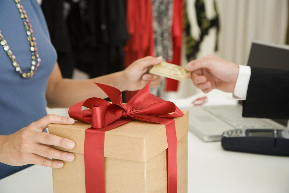 Woman accepting bank card from customer for gift boxed item, close-up