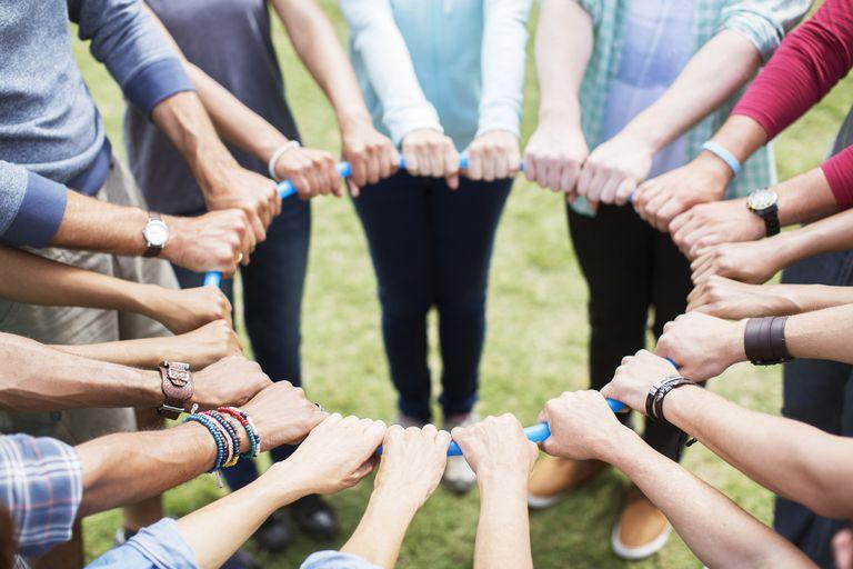 Team connected in circle around plastic hoop