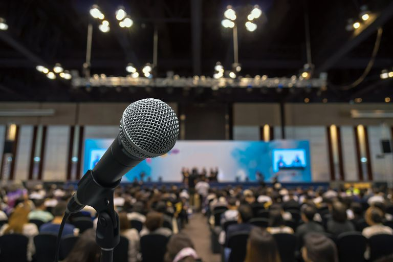 Microphone with blurred photo of conference hall with attendees in background
