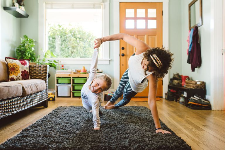 Mother and daughter doing yoga at home
