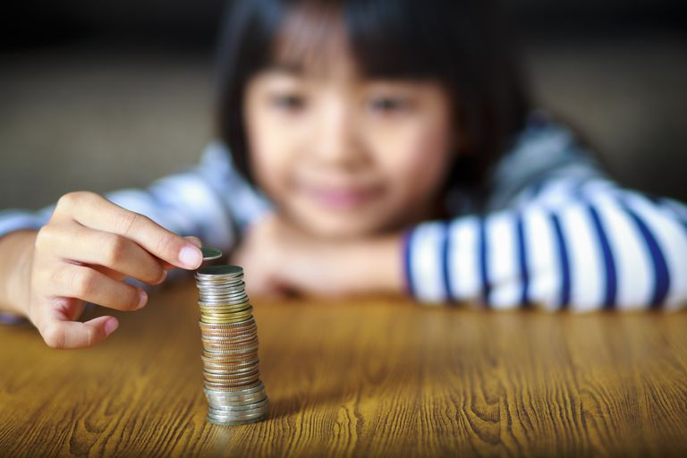 child with stack of coins