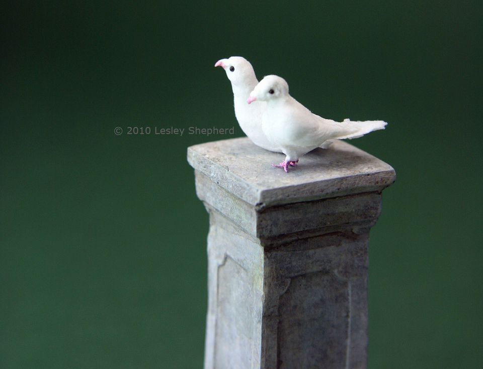 A sitting dove and a standing dove in dolls house scale.