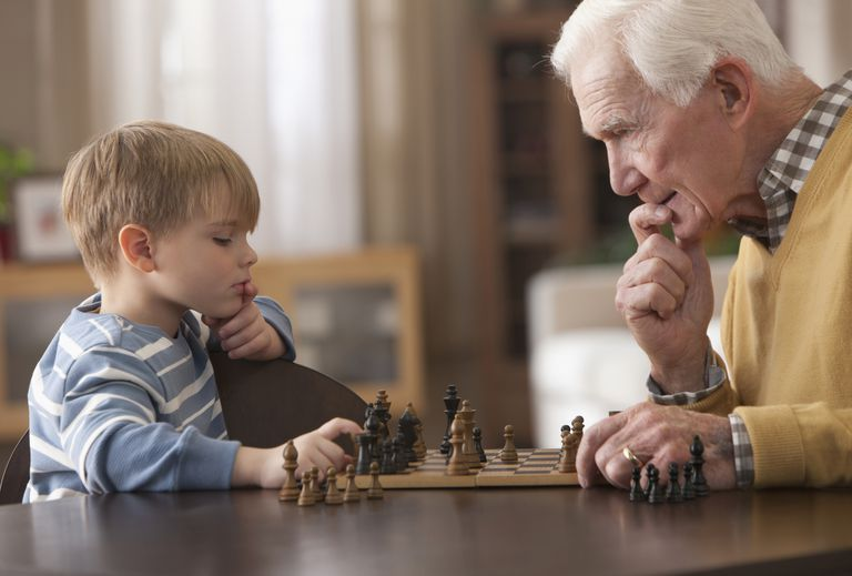 An older man playing chess with a young boy