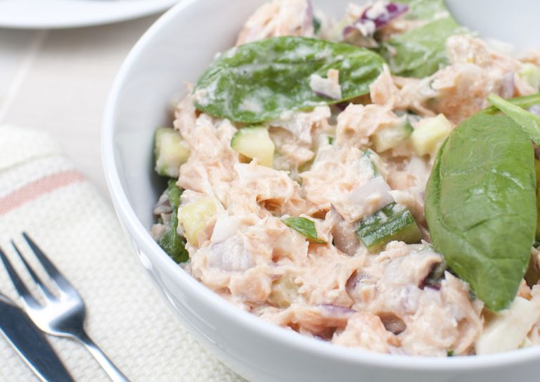 salmon salad in a bowl with spinach leaves