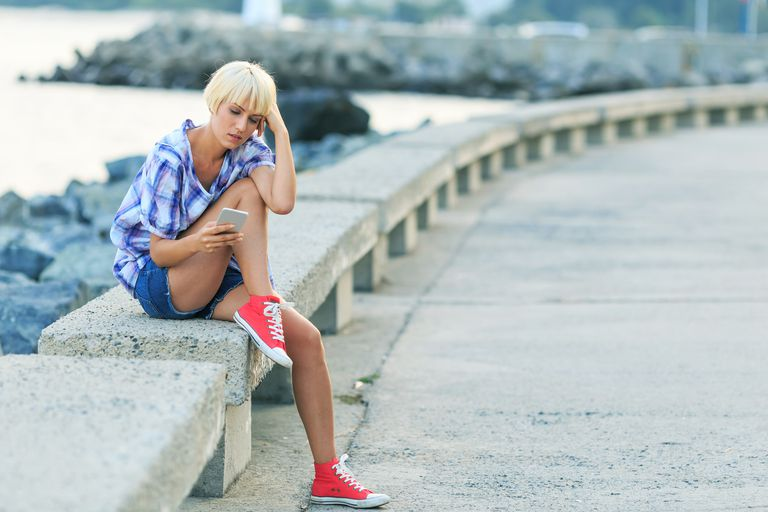 Sad young woman sitting on beach