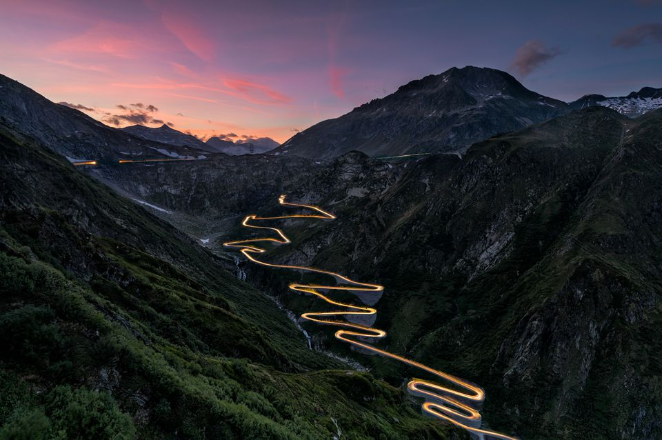 Gotthard Pass Road curves at sunset with traffic lights