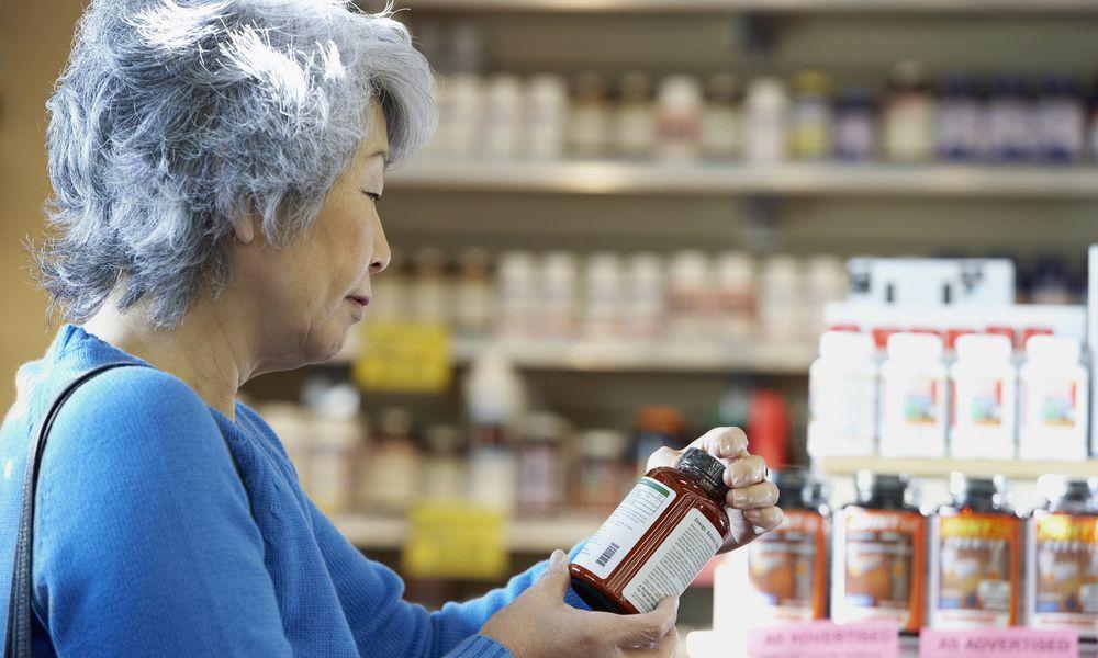 senior Asian woman looking at vitamin bottle in pharmacy