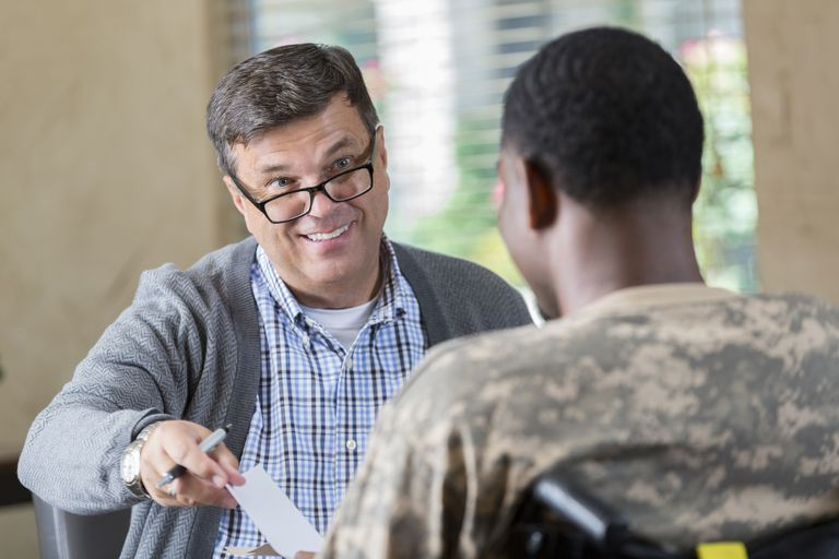 Doctor prescribing medication to young soldier during therapy session