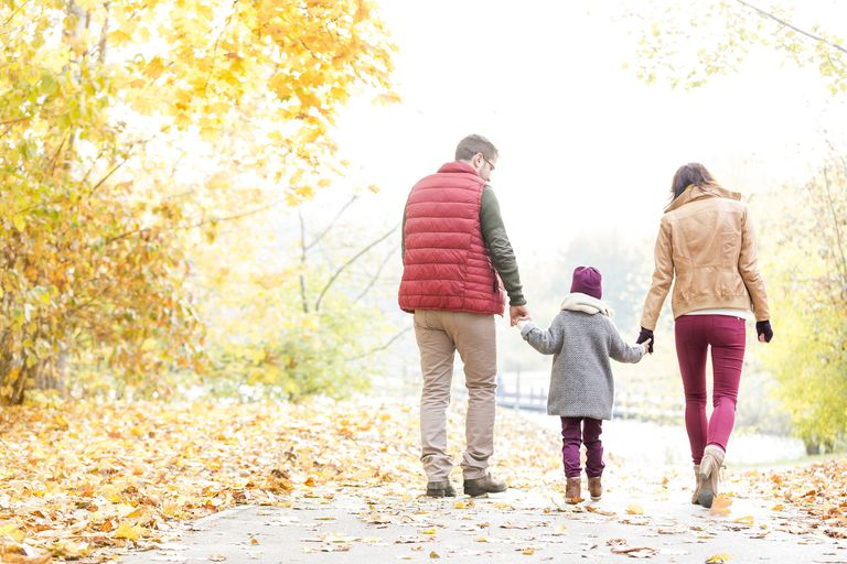 Family holding hands and walking in autumn park